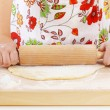 Woman rolling dough using rolling pin - Stockfoto