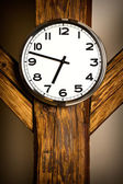 Wall clock hanging on wooden construction — Stock Photo