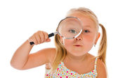 The little girl looking through a magnifying glass — Stock Photo