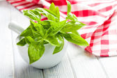 Fresh basil leaves in a mortar — Stock Photo