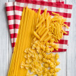Various raw pasta on kitchen table — Stockfoto