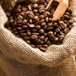 Coffee beans in canvas sack with wooden scoop — Stock Photo