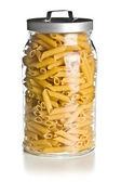 Raw penne pasta in glass jar — Stock Photo