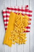 Various raw pasta on kitchen table — Stock Photo