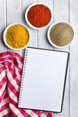 Diversas especiarias coloridas com livro de receitas em branco — Foto Stock