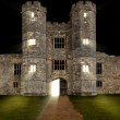 Old castle at night with lights shining through windows — Stock Photo