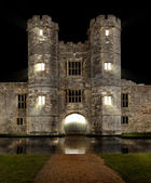 Castle at night with moat and lights shining — Stock Photo