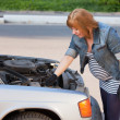 Royalty-Free Stock Photo: Pregnant Woman Trying to Repair the Car