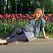 Pregnant woman sitting near tulip flowerbed — Stock Photo