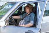 Pregnant woman in driving seat of the car — Stock Photo
