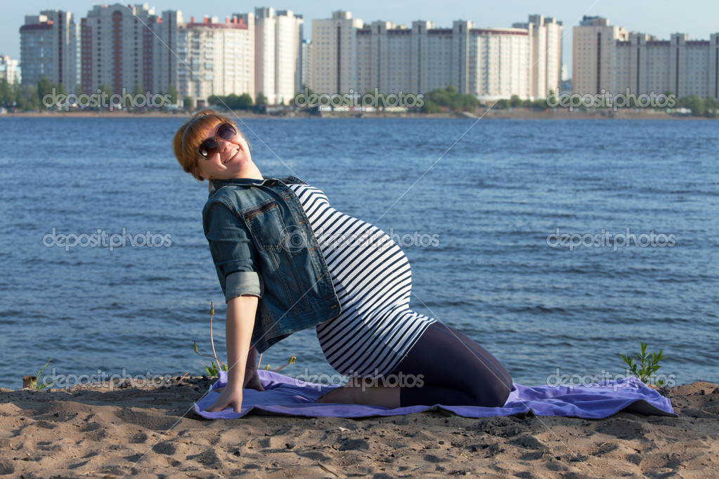 Pregnant woman doing gymnastic exercises on the river coast — Stock Photo #10784472