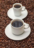 Cups with Hot Coffee on Coffee Beans — Stock Photo