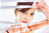 Kobieta patrzy przez żaluzje — Zdjęcie stockowe