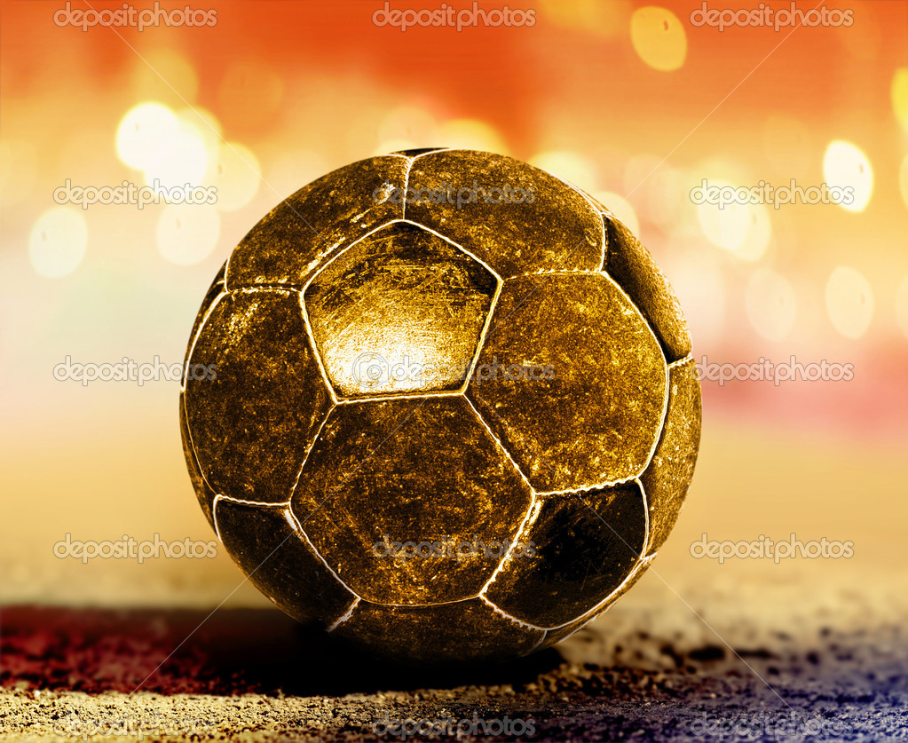 Golden soccer ball on ground of football field — Stock Photo #11084481