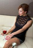 Vrouw in zwarte jurk op sofa ll — Stockfoto