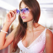 Girl tries on white fashion glasses - Stock Photo