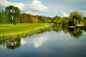 Idyllic golf course at the river — Stockfoto