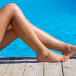 Sexy female legs at swimming pool - Stock Photo