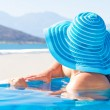 Stock Photo: Woman in hat relaxing at swimming poo