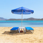 Blue deckchairs under parasol — Stock Photo #11645680