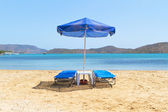 Blue deckchairs under parasol — Stock Photo