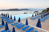Swimming pool with sunbeds at Mirabello Bay — Stock Photo