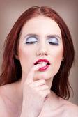 Beautiful women with nice make-up bitting her finger — Stock Photo