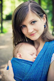Mother with newborn baby in a sling — Foto de Stock