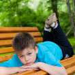 Stock Photo: Boy lay on bench
