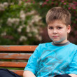 Sad boy sitting on a bench — Stock Photo