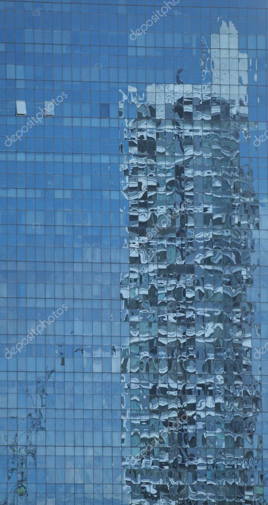 Panoramic view of skyscaper reflection on a blue glass building  Stock Photo #12022643