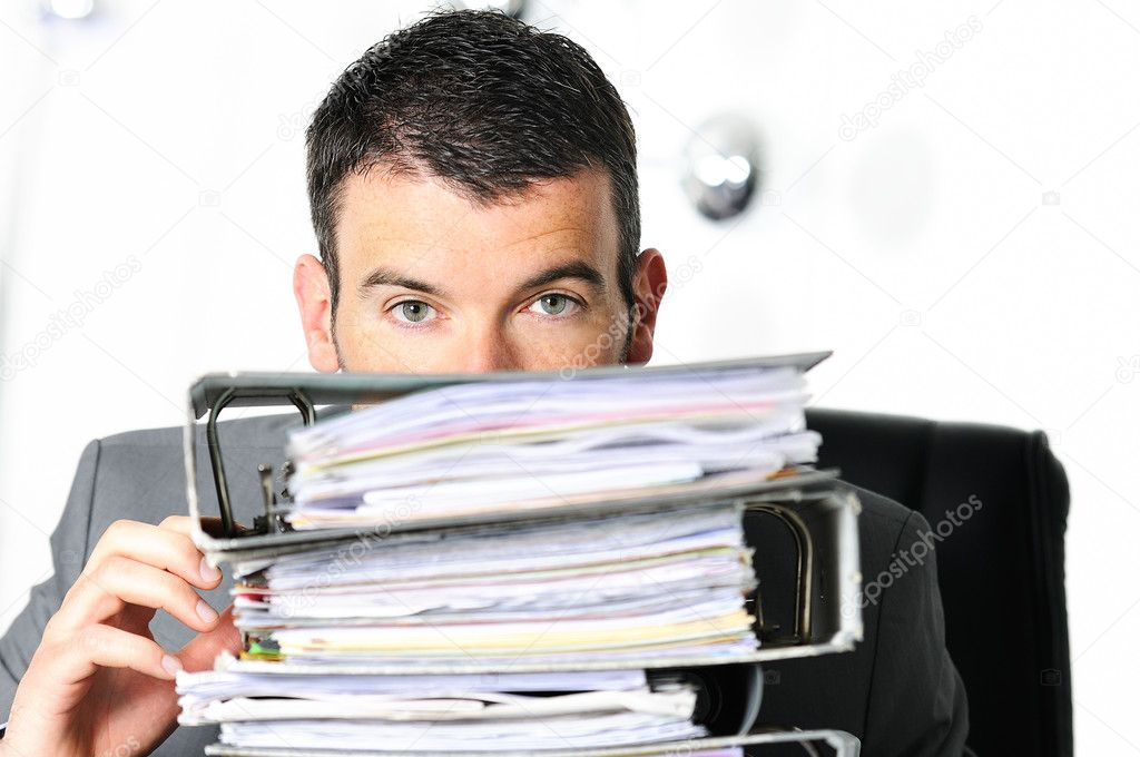 Busy man hiding behind a stack of files — Stock Photo #11828895