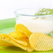 Crisp baked potato wedge in a bowl of sour cream — Stock Photo