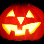Halloween pumpkin jack-o-lantern candle lit, isolated on black background — Stock Photo