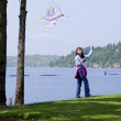 Foto Stock: Biracial asigirl flying kite by lake