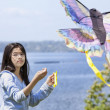 Biracial asian girl flying kite by the lake — Photo