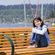 Stock Photo: Ten year old girl enjoying sun on bench by lake