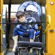 Disabled little boy on school bus wheelchair lift — Stock Photo #11616646