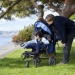 Father spending time with disabled son in wheelchair — Stock Photo