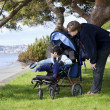 Stock Photo: Father spending time with disabled son in wheelchair