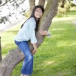 Young girl resting on a tree branch - Stock Photo
