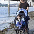 Father pushing wheelchair with disabled son on beach - Stock Photo