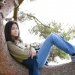 Stock Photo: Young teen girl relaxing on tree limb