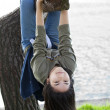 Stock Photo: Young teen girl hanging upside down on tree limb