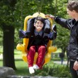 Father pushing disabled boy in special needs swing - Stock Photo