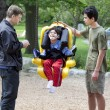 Disabled little boy swinging on special needs swing — Stock Photo