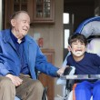 Elderly man in wheelchair laughing with disabled boy in kitchen - Stock Photo