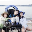 Sisters taking care of disabled brother on beach - Stock Photo