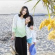 Two sisters standing on the beach - Stock Photo
