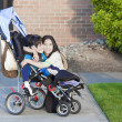 Disabled boy in wheelchair and his sister - Stock Photo